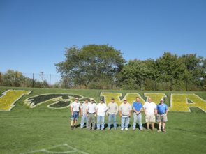 A group of men standing in front of IOWA painted in the grass on an athletic field.